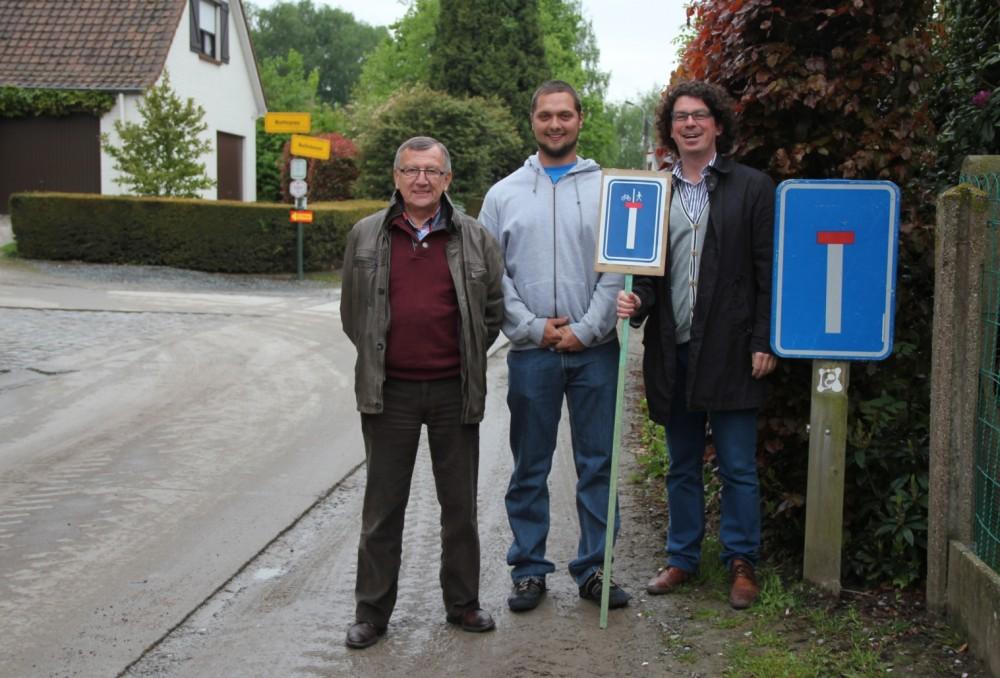 """Open Vld plus-raadsleden Guy De Smet, Ruben De Gusseme en Filip Michiels aan een oud verkeersbord met voorbeeld van nieuw bord """"doorlopende straat"""" in de hand (foto Open Vld plus)"""