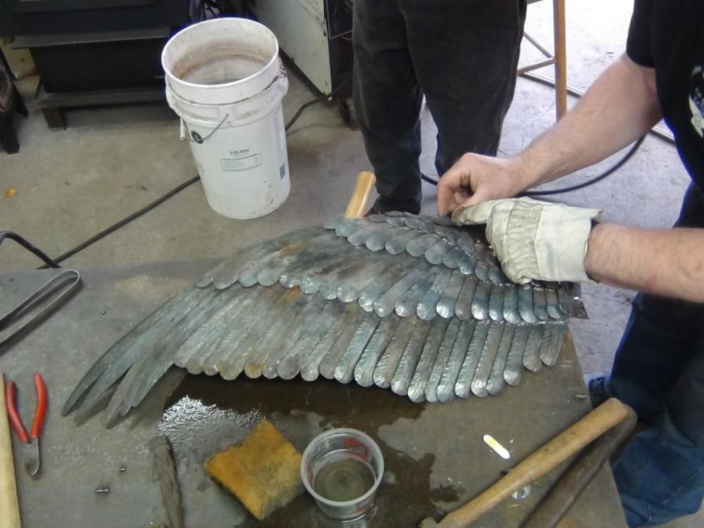 De veren op de bovenste vleugel zijn bijna volledig. Nu moeten er nog veren onder geplaatst worden.