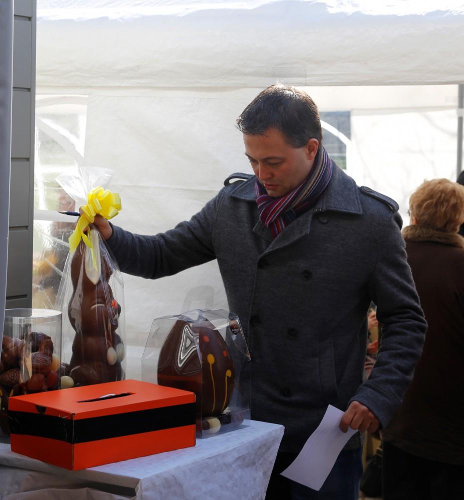 Egbert Lachaert, volksvertegenwoordiger uit Merelbeke, neemt deel aan de tombola en weegt de chocoladen stukken