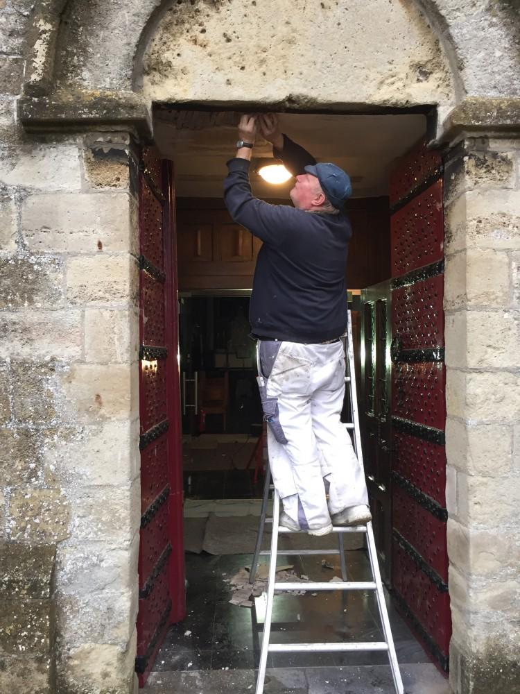 Fernand De Moor herstelt het pleisterwerk boven de deuren van de kerk