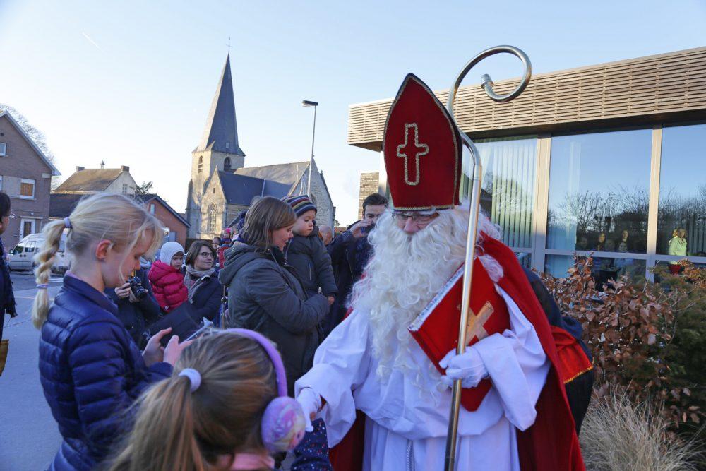 Sinterklaas groet de kinderen bij zijn aankomst aan 't IJzeren Hekken